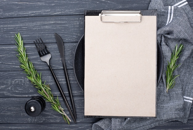 Clipboard on table with plate and cutlery