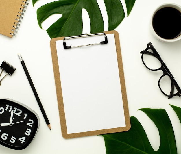 Clipboard and white paper on white office desk background. flat lay design.