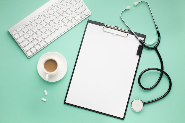 Clipboard; wireless keyboard; cup of coffee and stethoscope on green desk