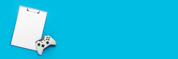 Буфер обмена с пустым листом и геймпадом на синем