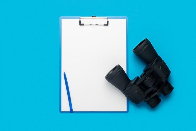 Буфер обмена с пустым листом и биноклем на синем