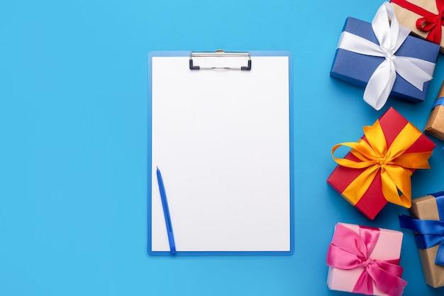 Буфер обмена с пустым листом и подарками, изолированными на синем