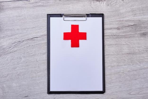 Буфер обмена с красным крестом. чистый лист бумаги на деревянных фоне. место для написания диагноза.