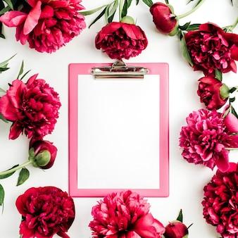 Буфер обмена с пустым пространством для копии в рамке из розовых пионов на белой поверхности