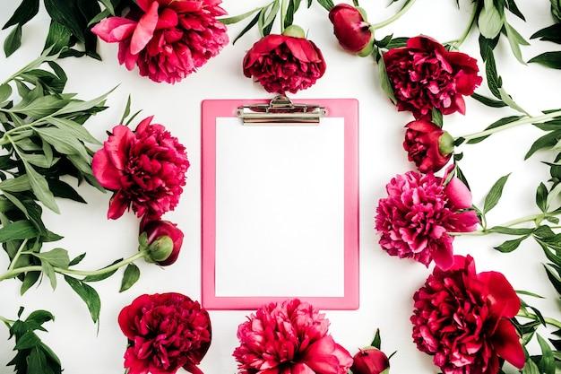 白い表面にピンクの牡丹の花のフレームに空白のコピースペースを持つクリップボード