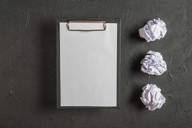 Clipboard with blank paper besides crumpled papers in a row