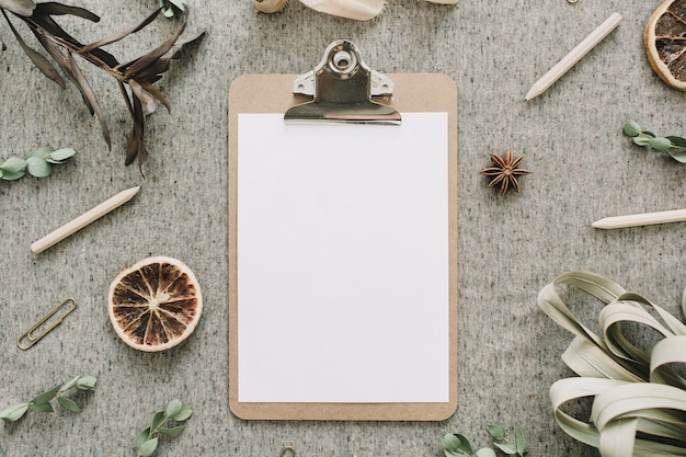 Clipboard with blank paper mock up in frame of eucalyptus branches, dried oranges and leaves, ribbon on beige blanket background. flat lay