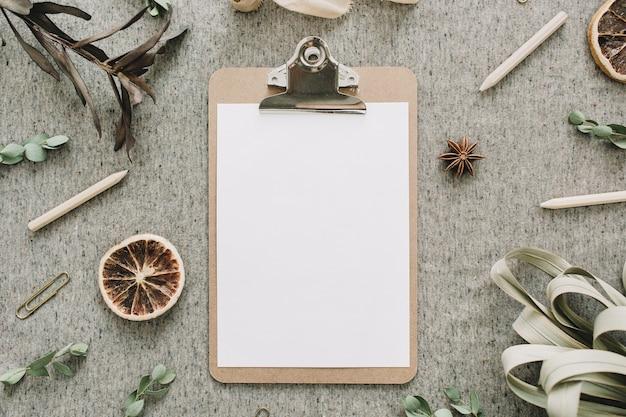 유칼립투스 가지, 말린 오렌지와 잎, 베이지 색 담요 배경에 리본의 프레임에서 빈 종이로 클립 보드. 플랫 레이