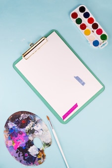 Clipboard with blank paper sheets,multicolored watercolor paints in box