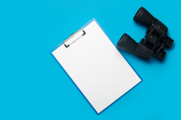 Clipboard with a blank sheet and binoculars on a blue
