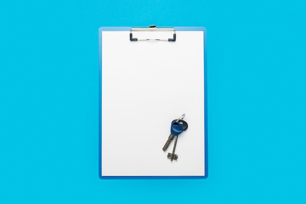 Clipboard with a blank sheet and keys to the house or apartment on a blue
