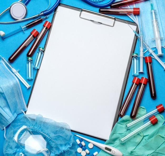 Буфер обмена с чистым листом бумаги с медицинскими инструментами на синем