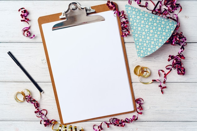 Clipboard with blank sheet of paper and party streamers on white wooden table, top view