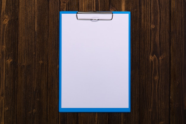 Clipboard with blank white paper sheet on wood