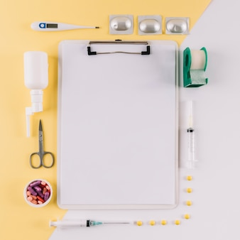 Clipboard with blank white paper surrounded by medical equipments on dual colored background