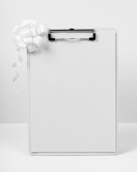 Clipboard with bow on white background