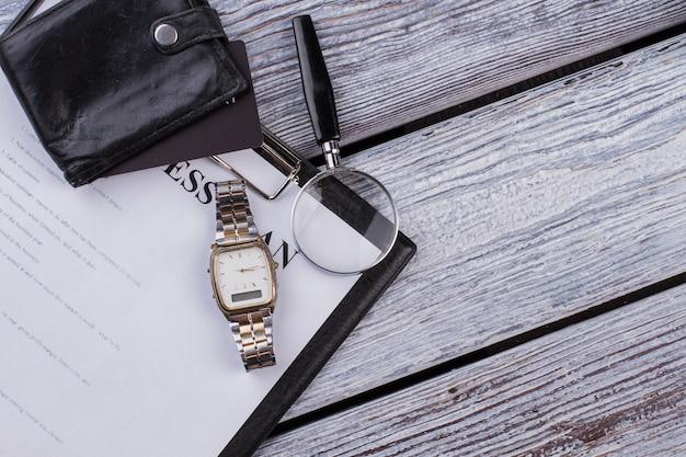 사업 계획이 있는 클립보드와 유리 돋보기가 있는 시계 시계. 흰색 나무 배경입니다. 평면도 평면도.