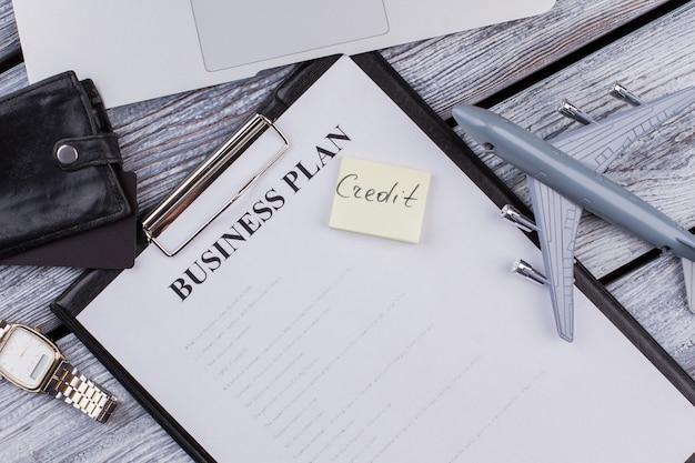 사업 계획과 신용 메모가 있는 클립보드. 나무 테이블에 비즈니스 액세서리입니다. 평면도 평면도.