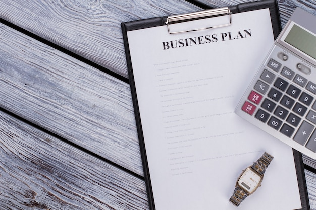 흰색 나무 테이블에 사업 계획 시트와 계산기가 있는 클립보드. 평면도 평면도.
