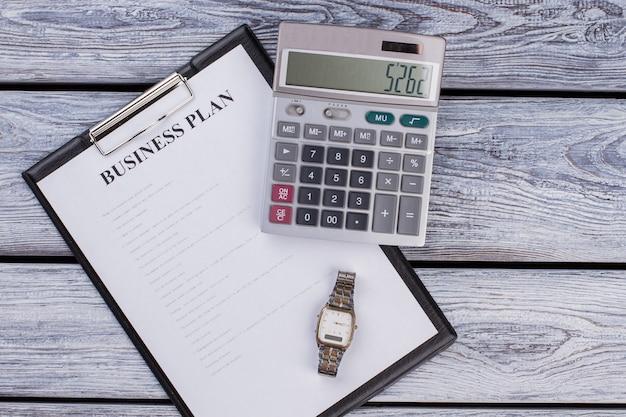 계산기와 시계 시계가 있는 사업 계획이 있는 클립보드. 평면도 평면도. 흰색 나무 테이블입니다.