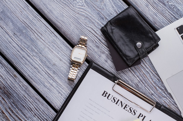 사업 계획과 고급 시계가 있는 클립보드. 흰색 나무 테이블에 사업가 액세서리입니다.