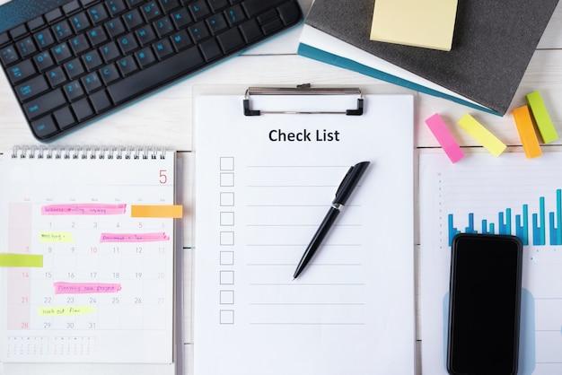 Доска сзажимом для бумаги с чистым листом контрольного списка с ручкой и умный телефон на документе с компьютером клавиатуры, календаре имеют план на памятке. вид сверху.