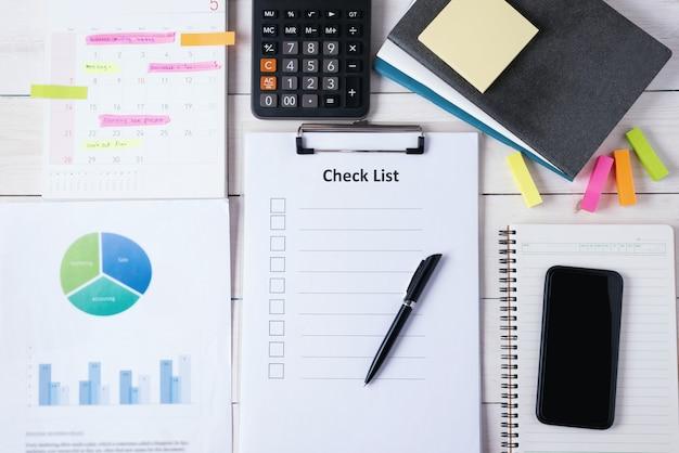 Доска сзажимом для бумаги с чистым листом контрольного списка с ручкой и умным телефоном на тетради с калькулятором и документом, календарем имеют план на памятке. вид сверху.