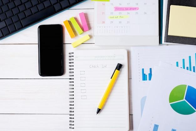 Доска сзажимом для бумаги с контрольным списком на тетради с ручкой и smartphone и документ с компьютером клавиатуры, календарем имеют план на памятке. вид сверху, плоская планировка.