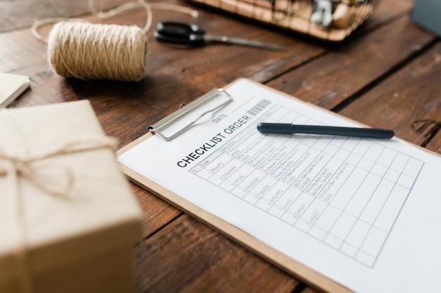 Буфер обмена с контрольным списком и ручкой среди катушки ниток, упакованной коробки и других предметов на деревянном столе
