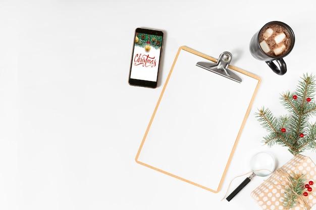 スマートフォンの画面にクリスマスの碑文付きクリップボード