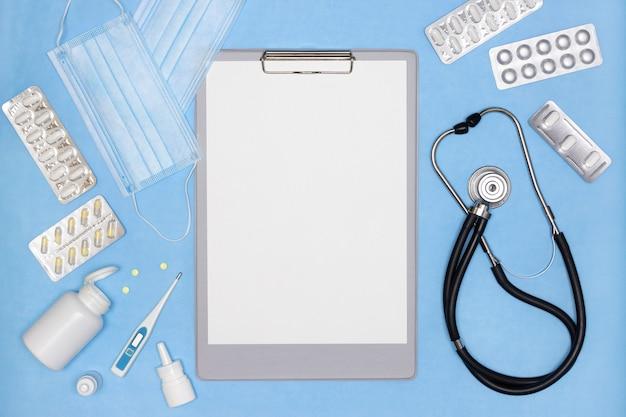 파란색 책상에 빈 종이 시트 청진기 온도계 의약품이 있는 클립보드