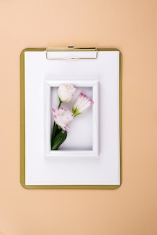 Clipboard with eustoma flower and white frame on beige surface, flat lay. post card mockup
