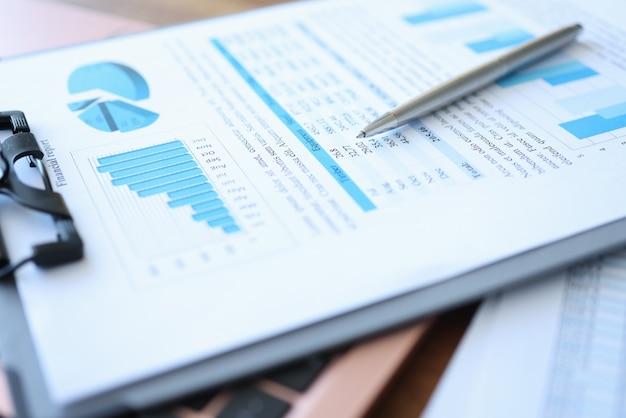 財務報告とペンが付いているクリップボードはテーブルの上にあります。中小企業の発展