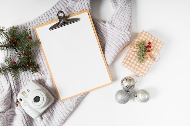Clipboard with gift box and baubles on table