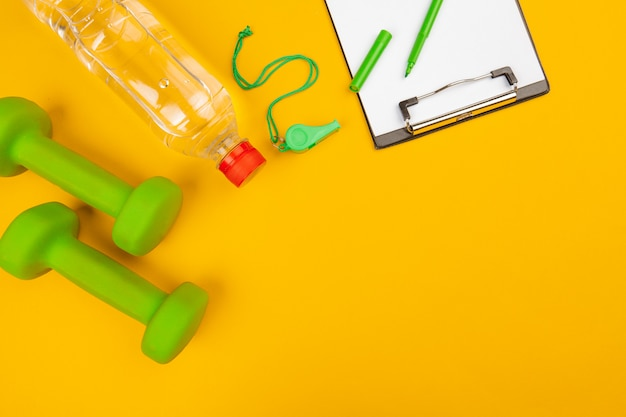 Clipboard with gym equipment dumbbell on yellow