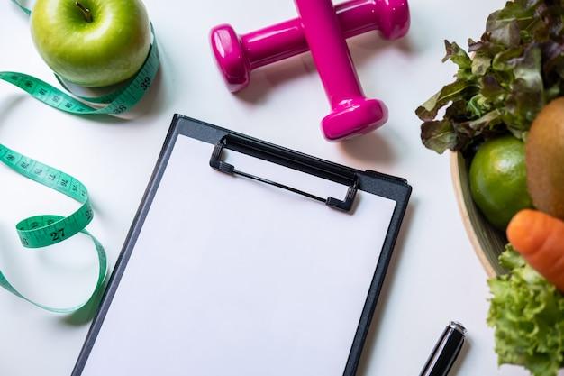 健康的な果物、野菜、栄養士の机、正しい栄養と食事の概念上の測定テープとクリップボード