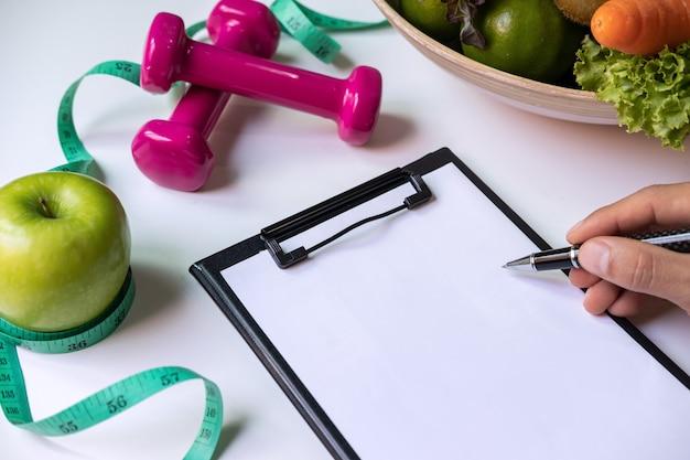 健康的な果物、野菜、栄養士の机の上の測定テープ、正しい栄養と食事のクリップボード