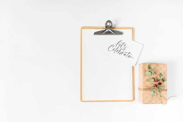 Clipboard with let's celebrate inscription on paper
