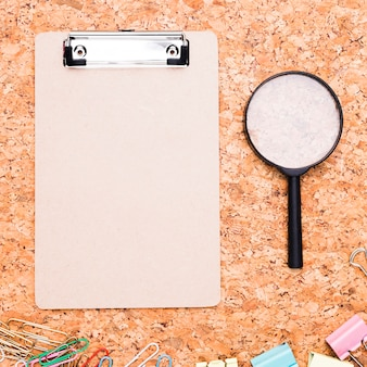 Clipboard with magnifier and multicolored paper clips on cork background