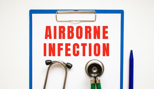 청진기와 펜이 있는 테이블에 페이지 및 텍스트 airborne infection이 있는 클립보드.