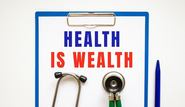 Буфер обмена со страницей и текстом здоровье - это богатство, на столе со стетоскопом и ручкой. медицинская концепция.