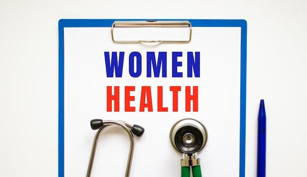 聴診器とペンでテーブルの上に、ページとテキストの女性の健康をクリップボード。医療の概念。