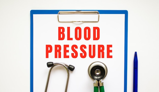 Clipboard with page and text blood pressure, on a table with a stethoscope and pen