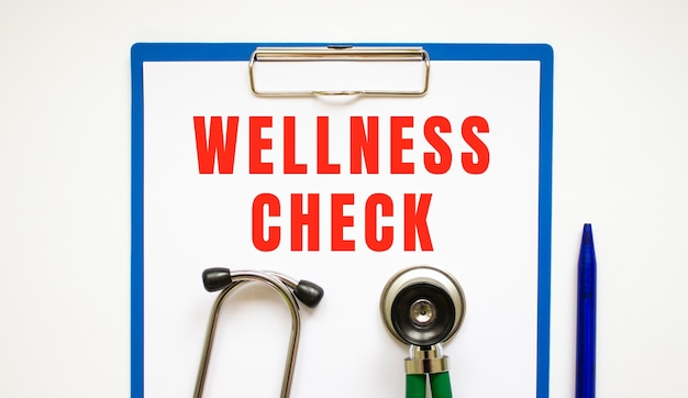 Clipboard with page and text wellness check, on a table with a stethoscope and pen.