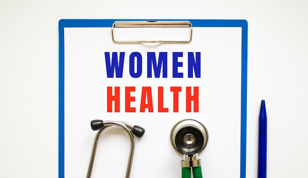 Clipboard with page and text women health, on a table with a stethoscope and pen. medical concept.
