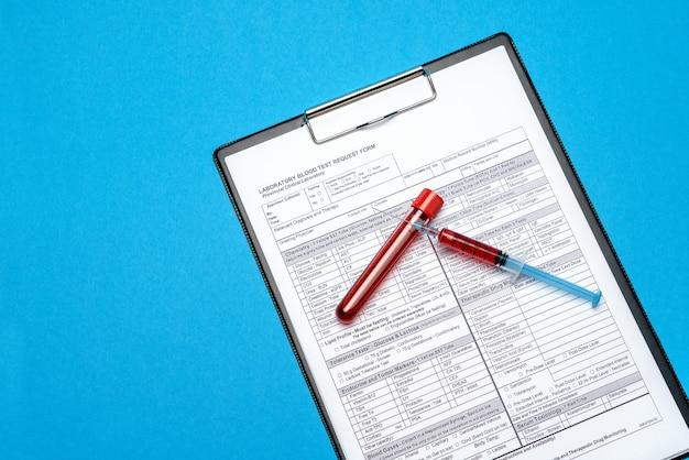 파란색 배경에 혈액 검사 튜브와 종이 빈 양식 클립 보드.