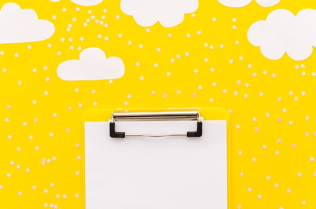 Clipboard with paper clouds on table