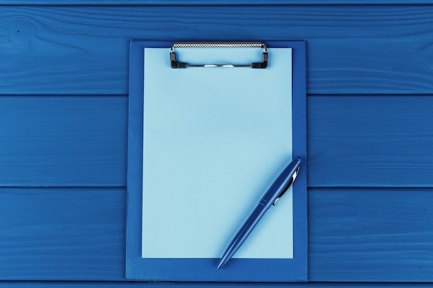 Clipboard with pen on blue