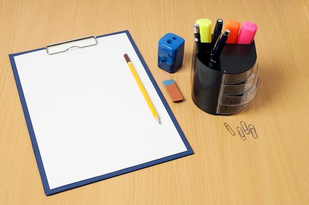 Буфер обмена с карандашом на деревянном столе и других письменных принадлежностях