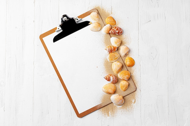 Clipboard with sea shells on wood table close up, copy space